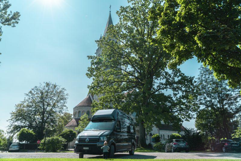 Bodensee, kleiner Junge vor dem Camper, Kirche und Bäume im Hintergrund
