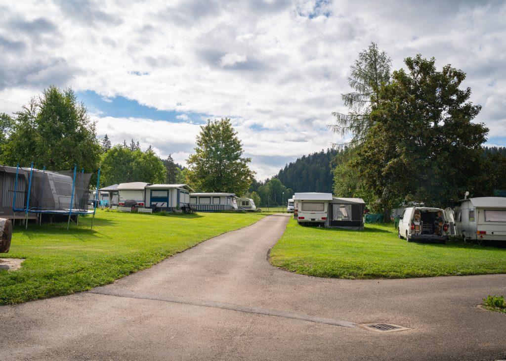 Wiesen-Stellplätze mit Campers und Trampolin, Wald im Hintergrund - Camping Jura