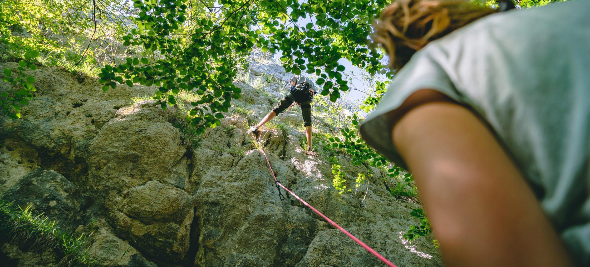 Frau sichert Partner an der Kletterwand - Kanton Jura