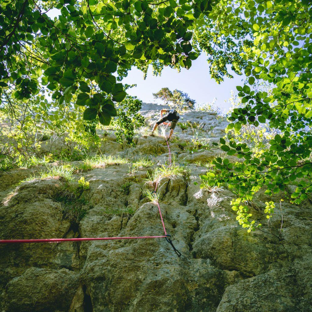 Gesicherter Kletterer an der Felswand - Bodenperspektive - Ferien im Jura