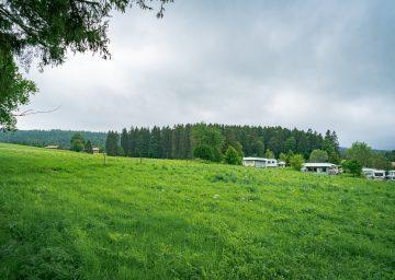 Camping Jura Schweiz - Grossflächige grüne Wiese vor dem Camping les Cerneux