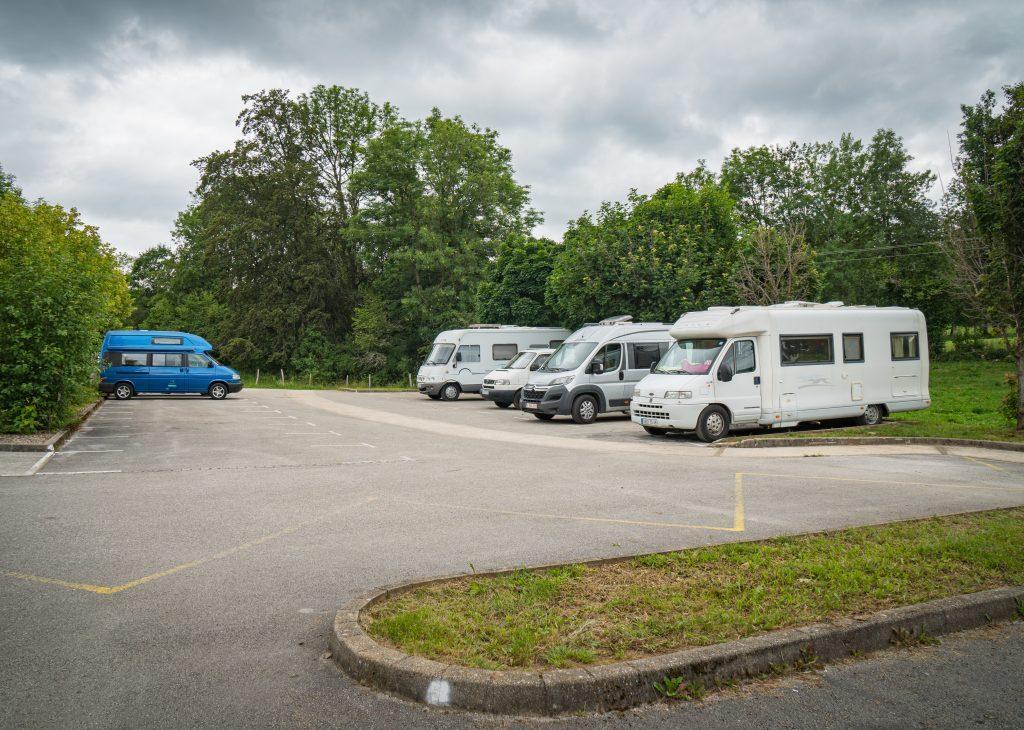 Fünf Campers auf Parkplatz des Wasserfall Doubs, bewölkter Himmel - Wandern Jura