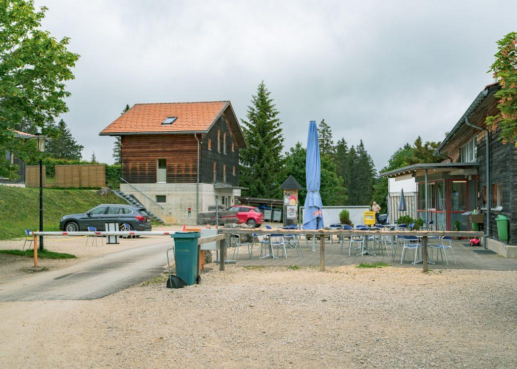 Aussenbereich vom Restaurant Camping les Cerneux mit Sitzplätzen und Parkplätzen im Jura