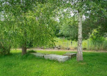 Sitzbank aus Stein auf grüner Wiese unter Bäumen - Camping Cerneux - Camping Jura Schweiz