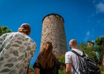 Drei junge Campers schauen zum Turm refous-porrentruy hinauf