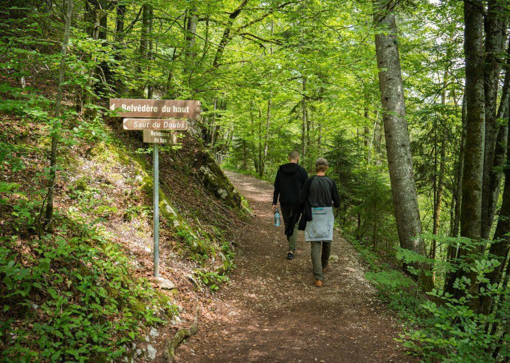 Zwei Männer gehen im Wald in Richtung Wasserfall-Doubs, davor Wegweiser - Wandern Jura