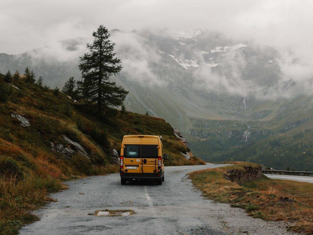 Camping Norditalien, gelber Camper auf dem Pass in regnerischer Landschaft