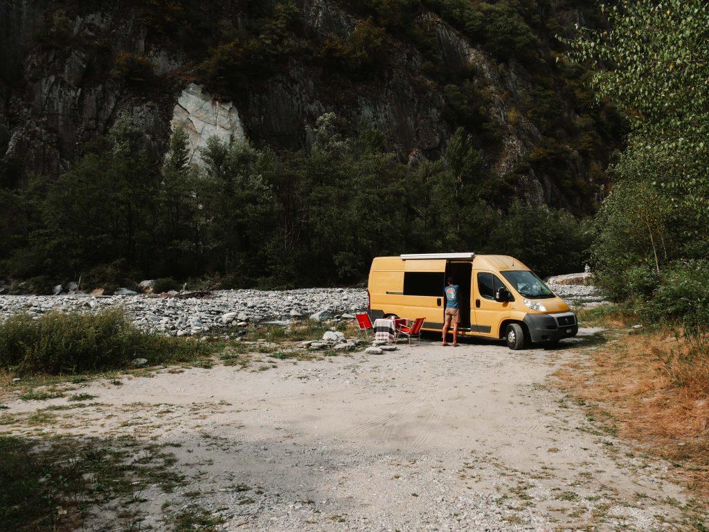 Camping Norditalien, gelber Camper vor Felsen
