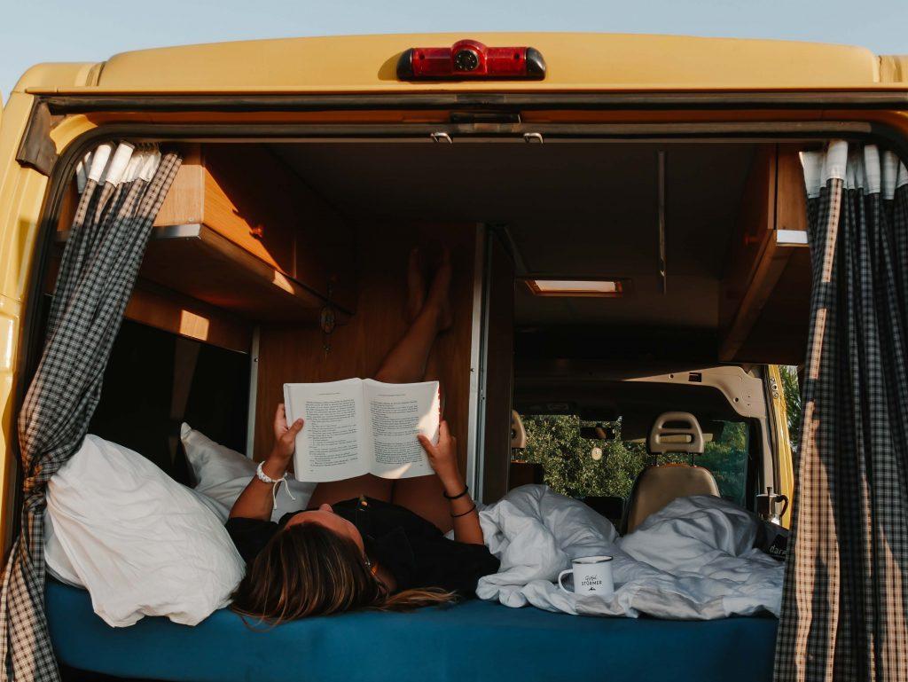 Camping Südfrankreich, Frau liegt im Camper und liest