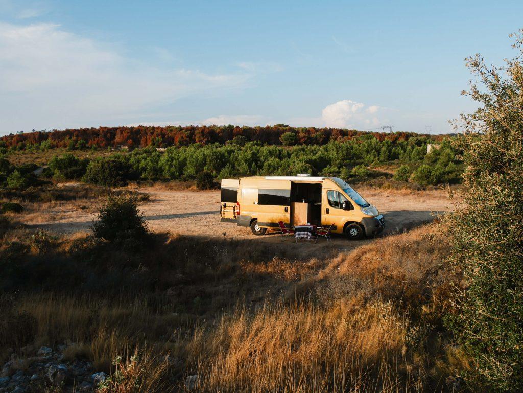 Camping Südfrankreich, gelber Camper in der trockenen Landschaft