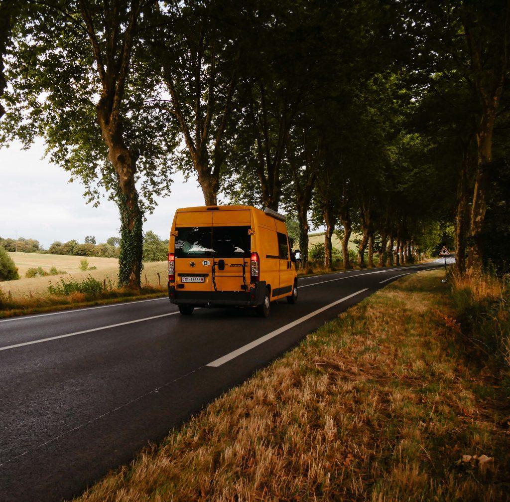 Camping Südfrankreich, fahrender gelber Camper in der Allee