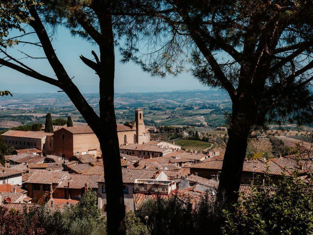 Rundreise Toskana, Blick zwischen Bäumen auf rote Gebäude von Siena